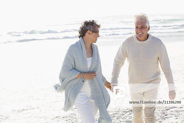 Ein Paar  das am Strand spazieren geht und sich an den Händen hält.