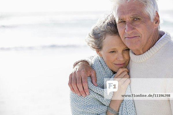 Nahaufnahme eines Pärchens  das sich am Strand umarmt.