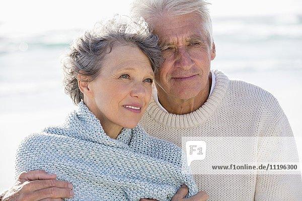 Älterer Mann  der seine Frau von hinten am Strand umarmt.