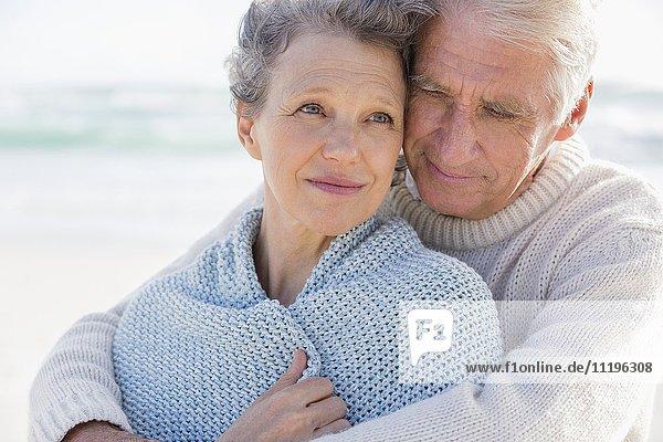 Aktiver älterer Mann  der seine Frau von hinten am Strand umarmt.