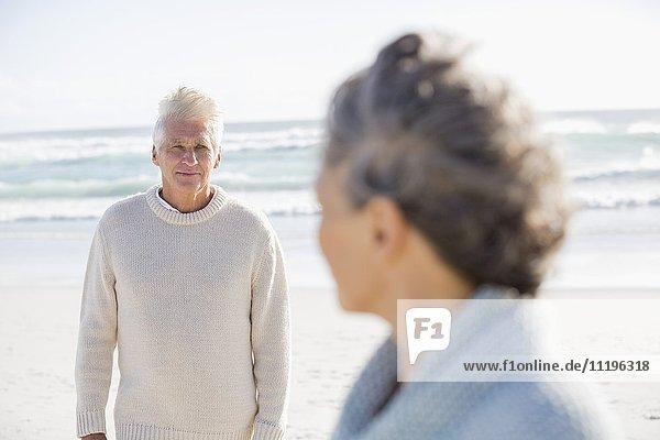 Älterer Mann schaut seine Frau am Strand an