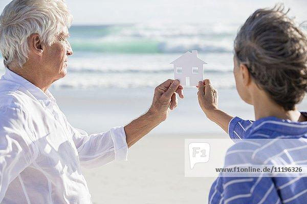 Nahaufnahme eines Paares mit einem Papierhaus am Strand