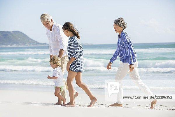 Altes Paar  das mit seinen Enkelkindern am Strand spazieren geht.