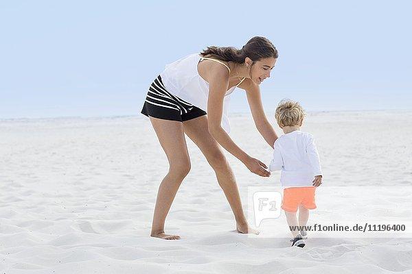 Frau spielt mit ihrem Sohn am Strand