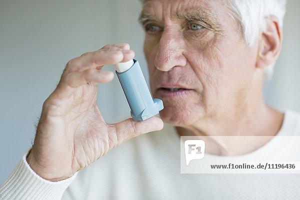 Nahaufnahme eines älteren Mannes mit Inhalator