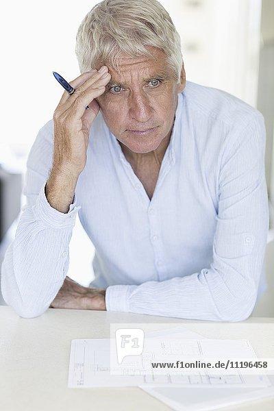 Nachdenklicher Senior mit Blaupause auf dem Tisch