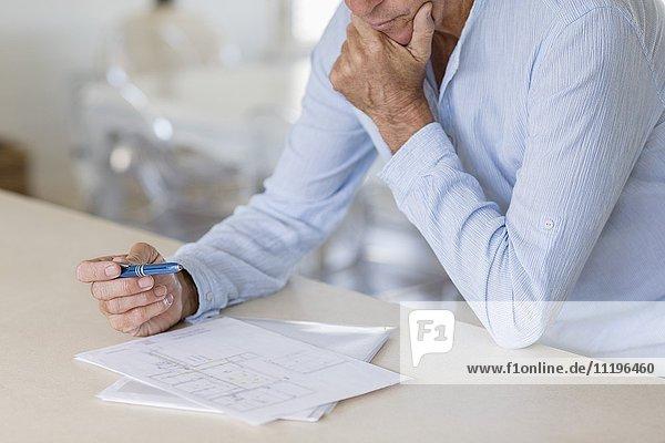 Älterer Mann untersucht Blaupause auf dem Tisch