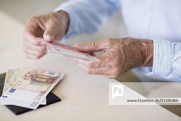 Mittelteilansicht eines älteren Mannes beim Zählen von Geldscheinen