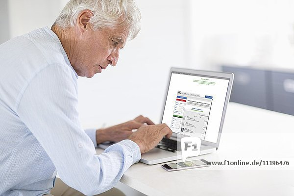 Senior Mann mit Laptop und Handy in der Küche