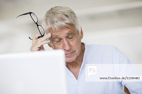 Müde Senior Mann Kopf in Hand mit Laptop auf dem Tisch