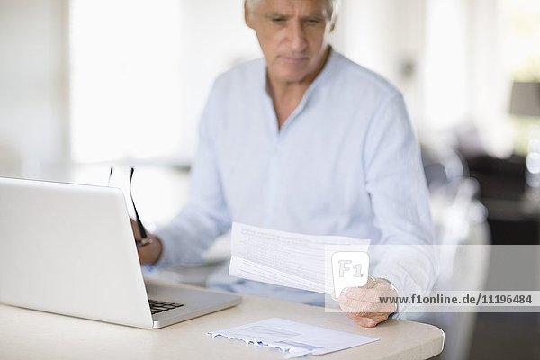 Senior Mann bezahlt Rechnungen online auf dem Laptop