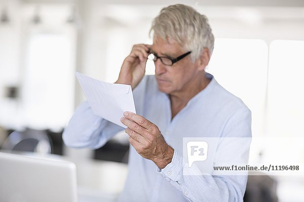 Senior man reading a letter with laptop on table