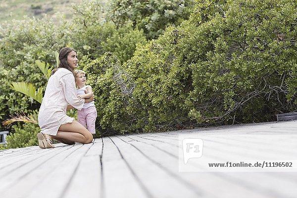 Glückliche Mutter und Sohn an Deck im Garten
