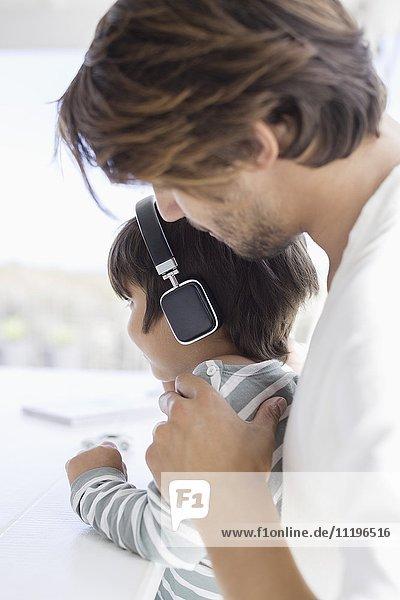 Junge hört Musik mit Kopfhörer mit Vater