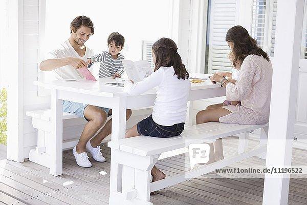 Glückliche junge Familie  die zu Hause zusammensitzt.