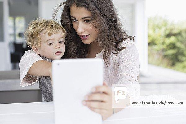 Mutter und Sohn nehmen Selfie mit digitalem Tablett mit nach Hause