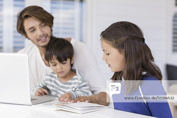 Vater lehrt die Kinder über die Weltkarte  während sie den Laptop zu Hause benutzen.