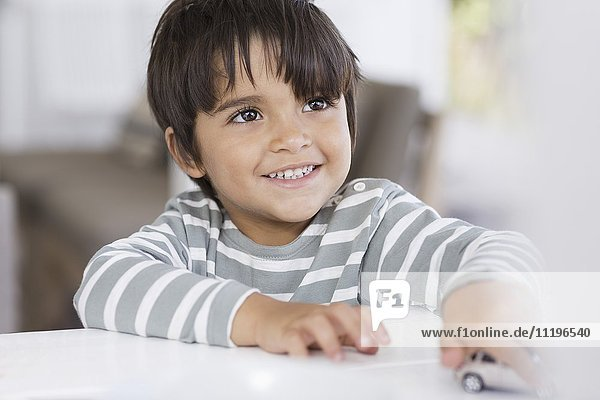 Boy playing with toy car in a living room