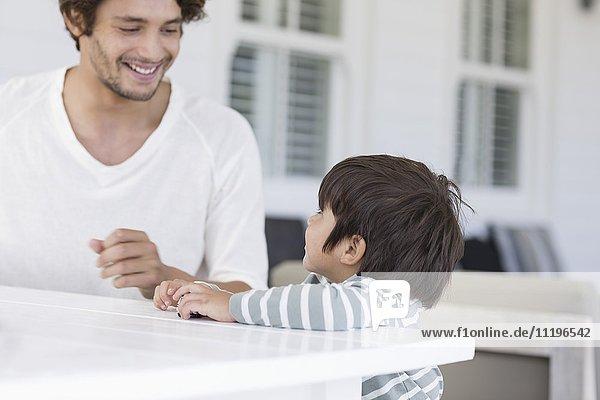 Vater und Sohn spielen mit Spielzeugauto im Wohnzimmer