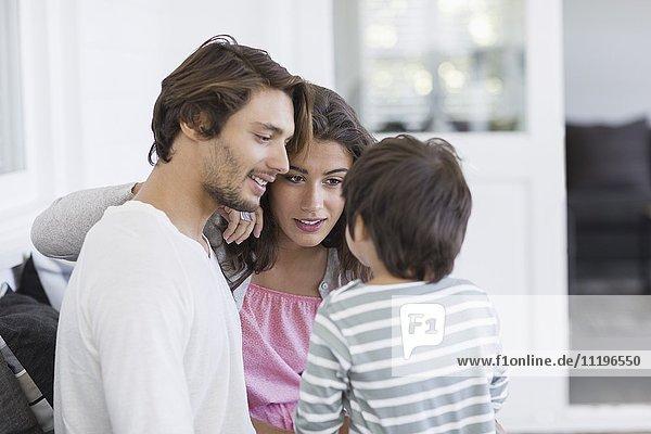 Glückliche junge Familie sitzt auf der Couch im Wohnzimmer