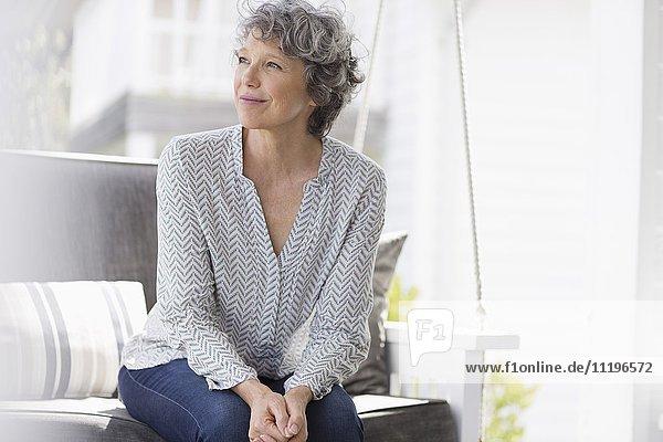 Frau auf einer Schaukel sitzend und träumend