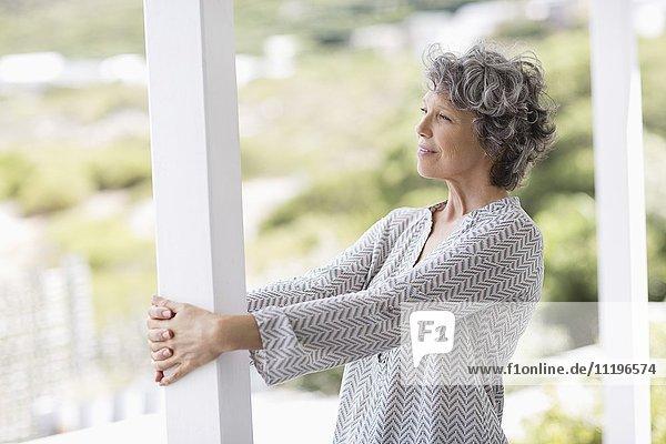 Nahaufnahme einer Frau  die sich an eine Säule lehnt und nachdenkt.
