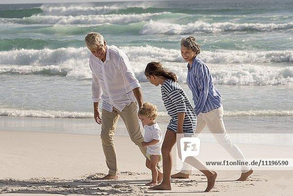 Glückliche Großeltern  die mit Enkelkindern am Strand spazieren gehen