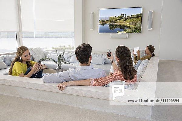 Rückansicht eines Paares  das mit seinen Töchtern fernsieht  die in verschiedenen Aktivitäten beschäftigt sind.