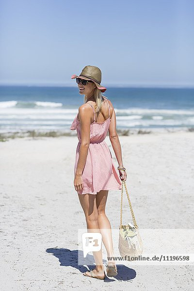 Rear view of a beautiful woman walking on the beach