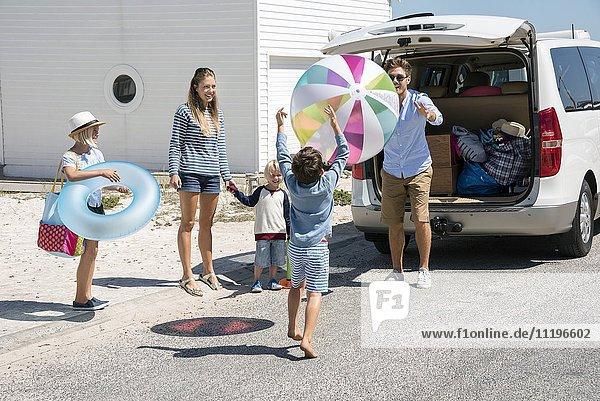 Fröhliches junges Familienpackauto mit Strandgetriebe für den Urlaub