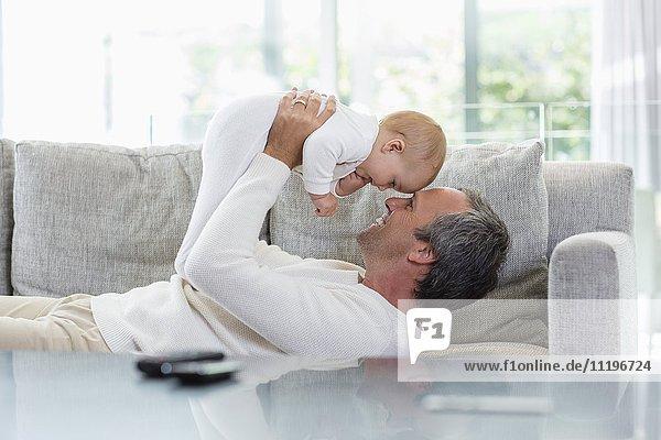 Glücklicher Vater spielt mit seiner süßen kleinen Tochter zu Hause.