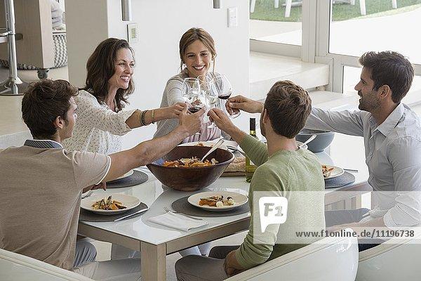 Glückliche Freunde  die zu Hause mit Weingläsern anstoßen.