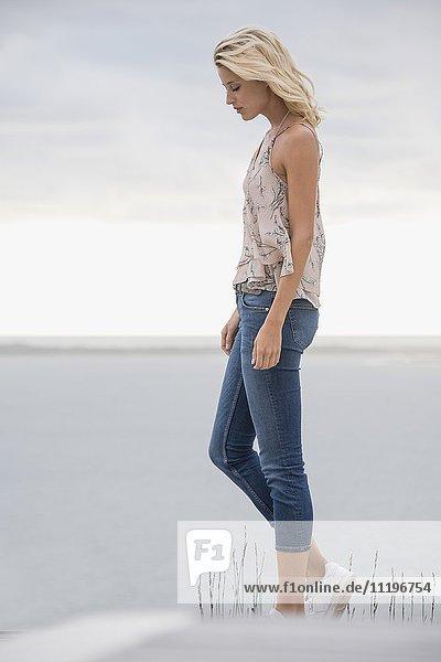 Schöne Frau beim Spaziergang am Seeufer