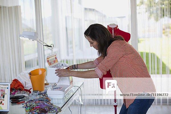 Profil des Modedesigners bei der Arbeit an der Nähmaschine