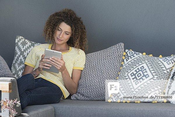 Frau auf einer Couch sitzend mit einem digitalen Tablett