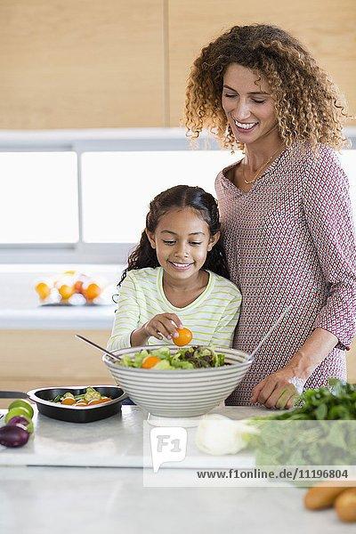 Glückliche junge Frau mit Tochter in der Küche