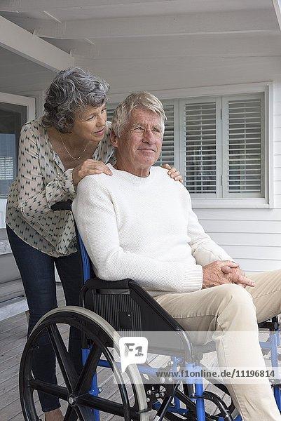 Senior im Rollstuhl mit seiner Frau auf der Veranda
