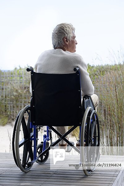 Senior man in wheelchair relaxing outdoors