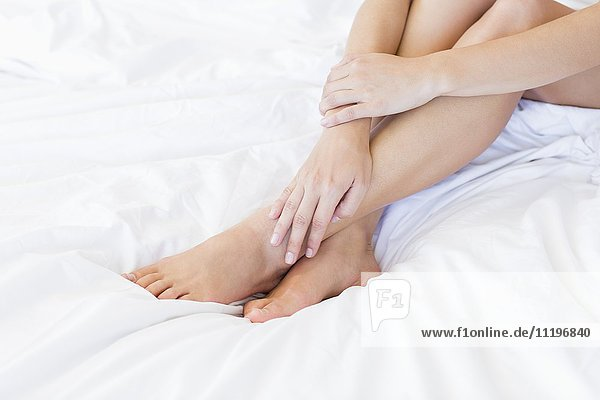 Low section view of a woman sitting on the bed