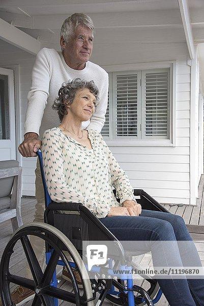 Senior Mann  der seiner Frau im Rollstuhl auf der Veranda assistiert.