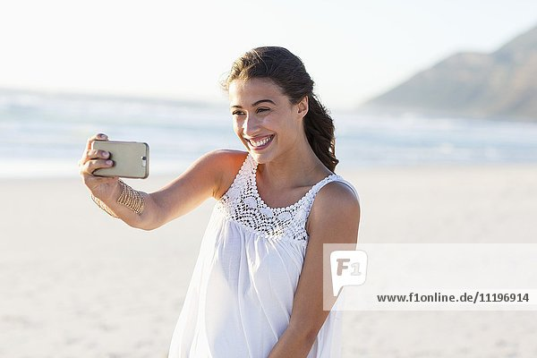 Attraktive junge Frau  die Selfie mit Smartphone am Strand nimmt