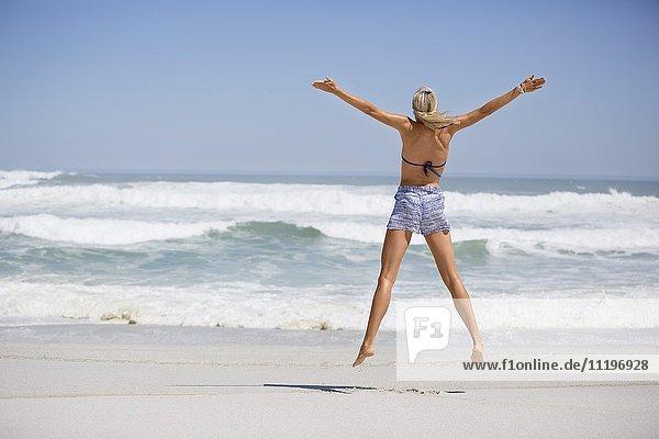 Junge Frau beim Springen am Strand