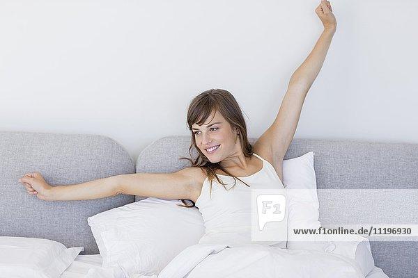 Glückliche  verschlafene Frau  die aufwacht und mit einer Dehnung gähnt  während sie im Bett sitzt.