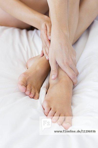 Flachschnittansicht einer auf dem Bett sitzenden Frau