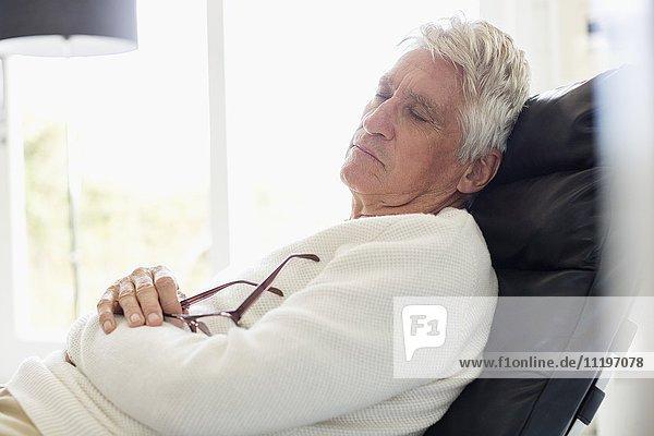 Senior Mann schläft auf Stuhl