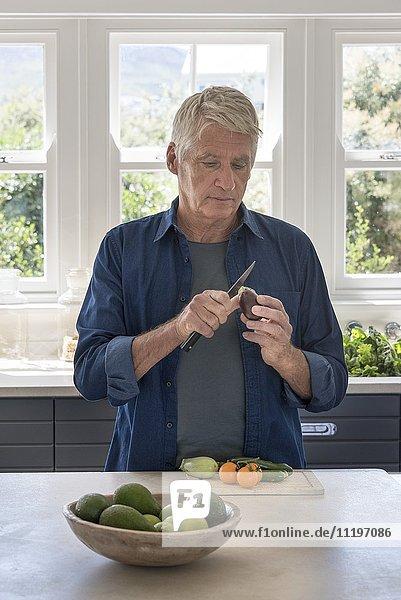 Senior Mann beim Zubereiten von Gemüse in der Küche
