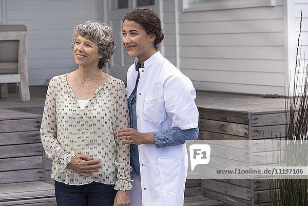 Glückliche Krankenschwester unterstützt ältere Frau im Pflegeheim