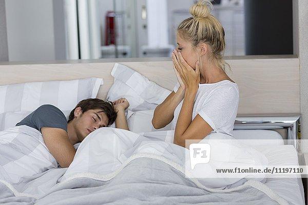 Junge Frau schaut ihren Mann an  der auf dem Bett schläft