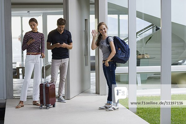 Teenagermädchen winkt mit ihren Gästen auf der Tür.
