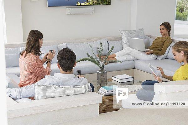 Familie im Wohnzimmer beschäftigt in verschiedenen Aktivitäten